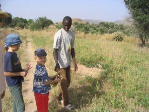 Timon hält frisch geerntete Erdnüsse in der Hand – rechts das Feld
