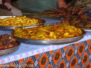 Frittierte Kochbananen (vorn) und Kartoffeln (hinten), Fleischspieße