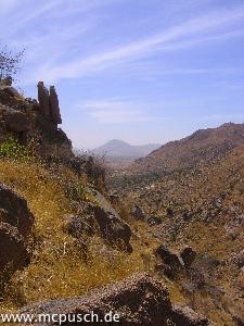 Blick in ein Seitental, links oben ein bedrohlich wirkender Felsen