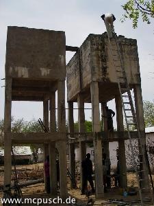 Zwei Wassertürme aus Beton stehen Seite an Seite.